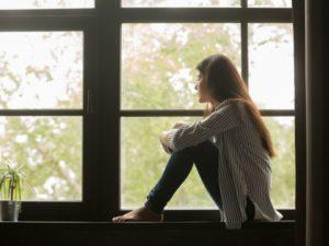 sad girl sitting by the window